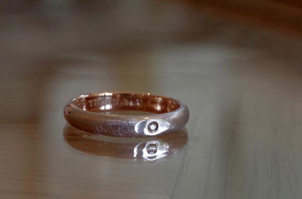 フラットな面に石留めしたコンビの婚約指輪