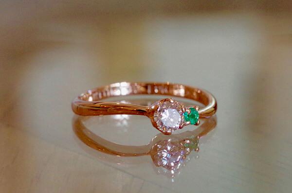 ダイヤにエメラルドが寄り添う婚約指輪