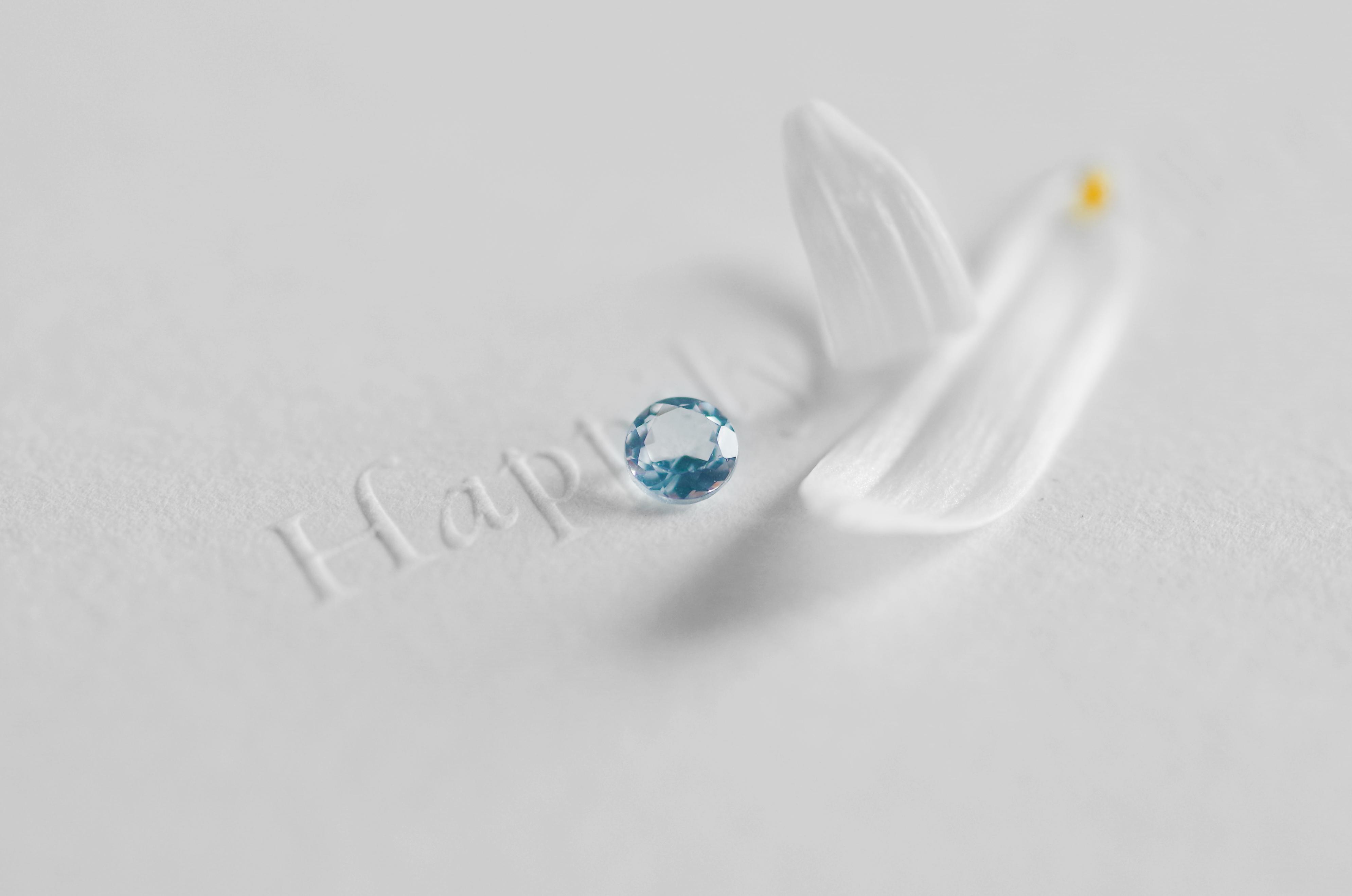 アクアマリンの裸石と白い花びら