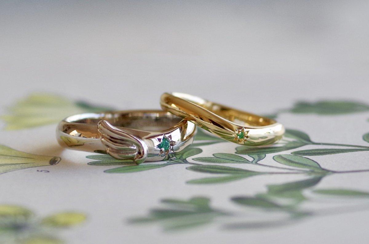 羽を携えたゆるいV字の結婚指輪
